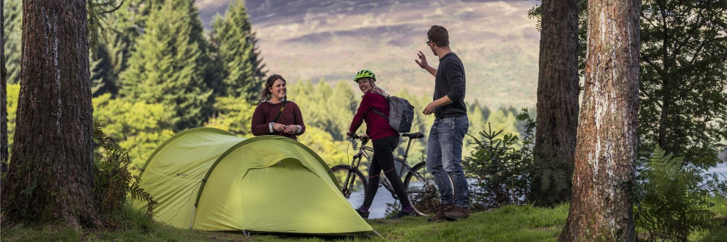 young-couple-pitching-green-tent-at-three-lochs-forest-drive-wave-hello-to-passing-woman-cyclist