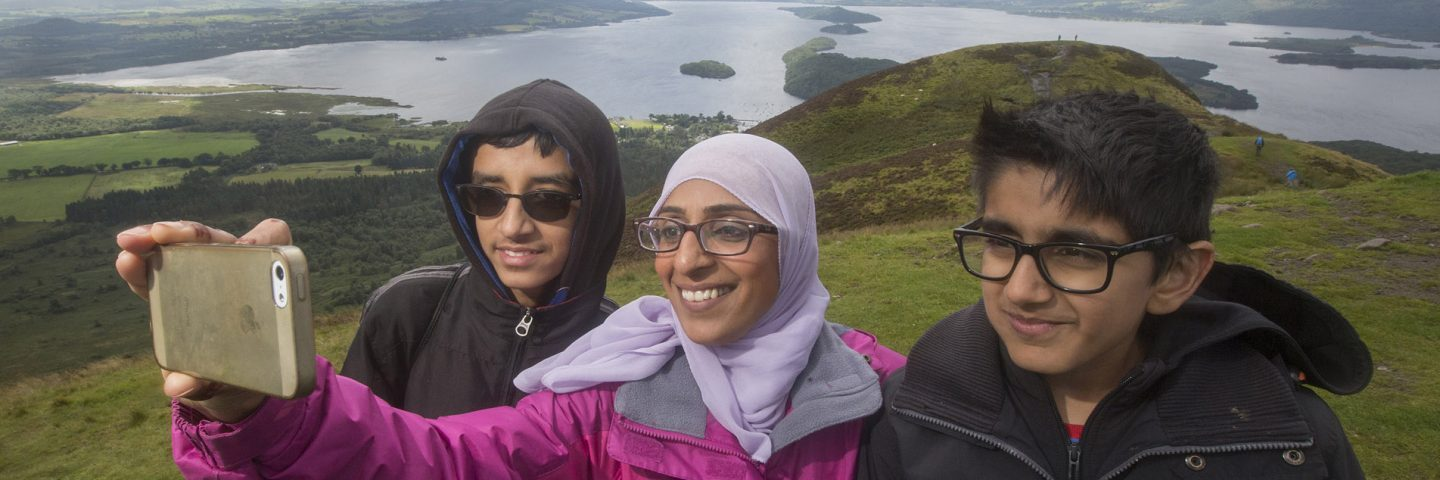 woman-wearing-glasses-and-hijab-taking-selfie-of-her-and-two-younger-boys-on-slopes-of-conic-hill-with-loch-lomond-and-islands-behind