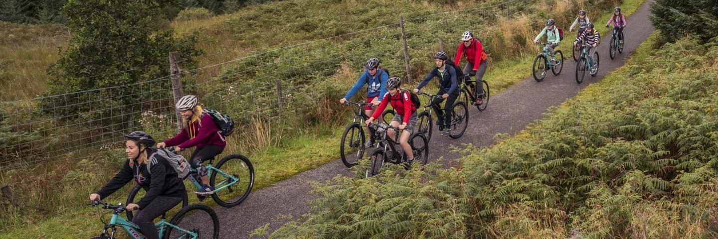 group-of-young-people-in-colourful-clothes-riding-on-bikes-on-national-cycle-route-seven-in-glen-ogle