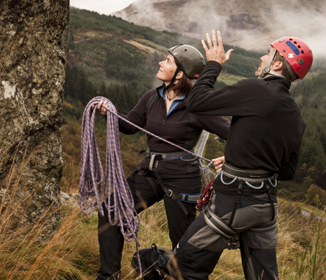 woman-and-man-in-climbing-gear-holding-rope-assessing-rock-wall-in-misty-glen-coniferous-forest-in-distance