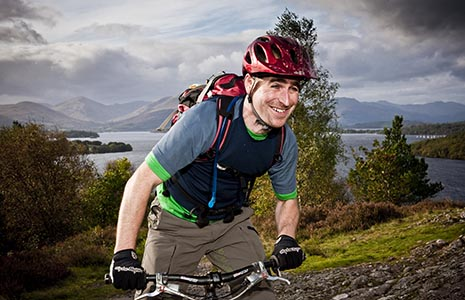 happy-cyclist-on-bike-wearing-helmet-going-uphill-with loch-lomond-trees-and-hills-behind