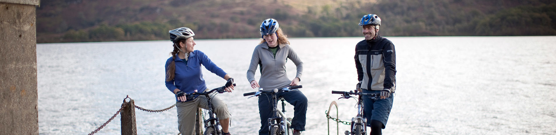 two-women-and-man-on-bikes-with-helmets-on-at-the-edge-of-pier-with-loch-behind-them