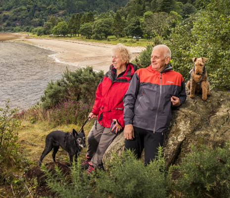older-couple-with-two-dogs-looking-into-distance-by-large-rock-ardentinny-beach-and-forest-behind-them