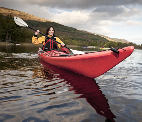 smiling-woman-peddling-red-kayak-on-loch-lomond