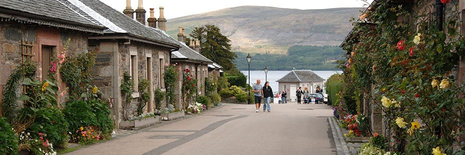 luss-village-pier-road-with-loch-lomond-and-tourists-in-the-distance-and-stone-houses-decorated-with-flowers-on-both-sides-of-the-road