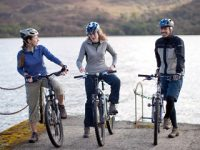 three-cyclists-two-women-one-main-with-bikes-and-helmets-on-edge-of-pier-loch-behind-them
