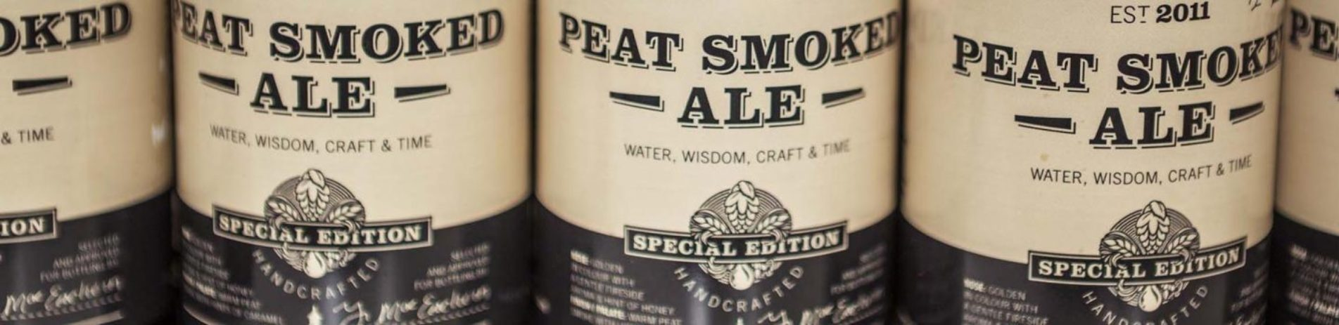 close-up-on-bottle-tags-reading-peat-smoked-ale-est-two-thousand-eleven-water-wisdom-craft-and-time
