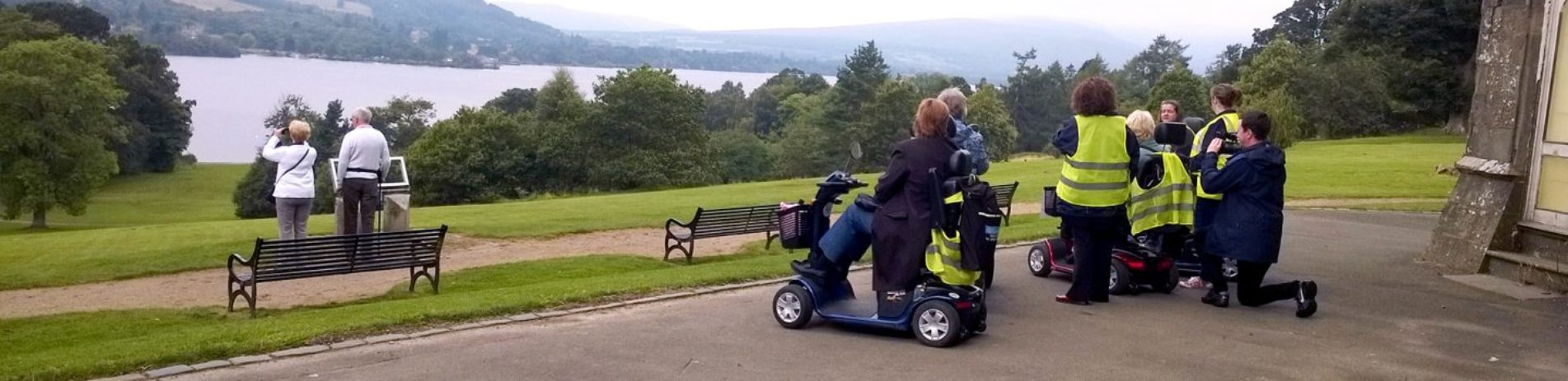 mobility-scooter-drivers-accompanied-by-people-in-high-viz-jackets-looking-into-distance-to-loch-lomond-from-balloch-castle