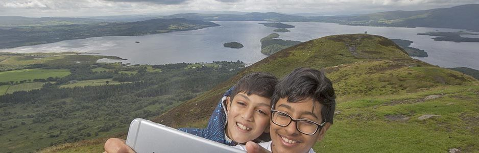 two-young-boys-smiling-and-taking-a-selfie-on-conic-hill-with-loch-lomond-behind