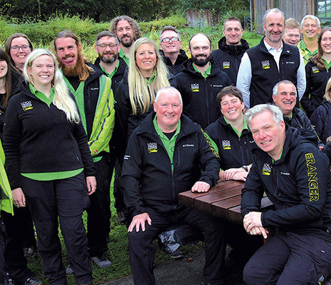 loch-lomond-trossachs-national-park-authority-large-group-of-staff-smiling-wearing-black-uniforms-and-green-shirts