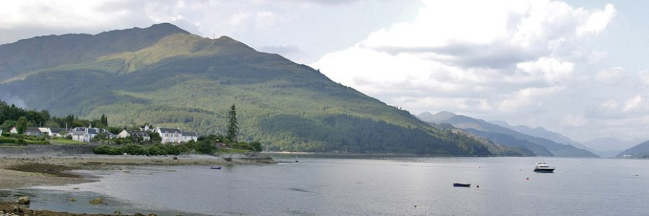 ardentinny-village-on-the-shore-of-loch-long-with-forested-hills-towering-above-and-arrochar-alps-profiling-in-the-distance