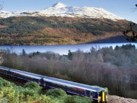 train-crossing-landscape-above-tarbet-with-ben-lomond-towering-above-loch-lomond-in-the-distance