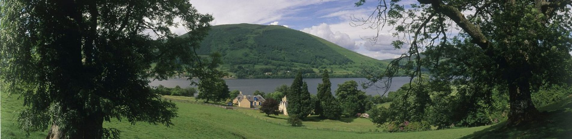 looking-through-trees-across-to-loch-earn-and-lochearnhead-village-forested-hills-in-the-background-blue-skies-with-some-clouds-above
