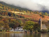 port-of-menteith-village-and-church-on-shore-of-lake-of-menteith-in-autumn-stunning-colours