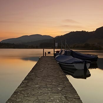 ferry-pier-at-sunset-at-lake-of-menteith-with-moored-boats-one-end-and-hills-in-the-distance