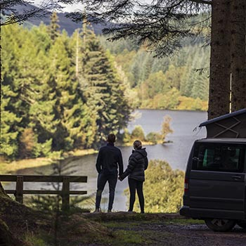 young-couple-holding-hands-admiring-stunning-loch-and-forests-view-on-high-ground-next-to-campervan-at-three-lochs-forest-drive-site