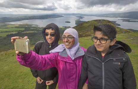 woman-wearing-white-hijab-and-glasses-and-with-two-young-boys-with-glasses-takes-selfie-loch-lomond-visible-behind-them-and-blue-banner-underneath-reads-our-vision