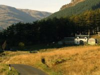 glen-massan-path-in-sunset-light-farm-house-in-distance-next-to-coniferous-plantation