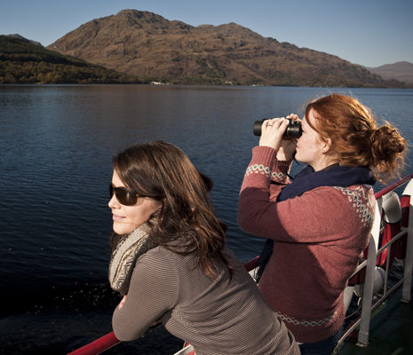 two-women-on-boat-deck-look-over-loch-lomond-water-one-through-binoculars