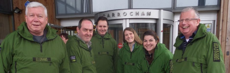 six-national-park-volunteer-rangers-in-green-jackets-and-smiling-at-camera-outside-headquarters