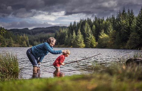 woman-with-child-ankles-in-water-loch-drunkie-three-lochs-forest-drive-coniferous-forests-visible-in-the-background