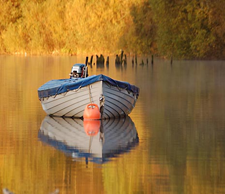 moored-boat-on-mirror-like-water-surface-with-autumn-tree-colours-behind