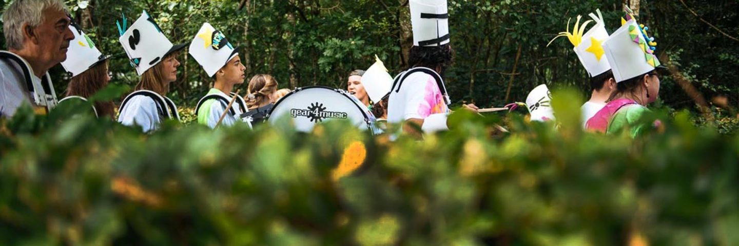 group-playing-drums-in-procession-and-wearing-tall-white-hats-beyond-green-hedges-at-balloch-festival-two-thousand-eighteen
