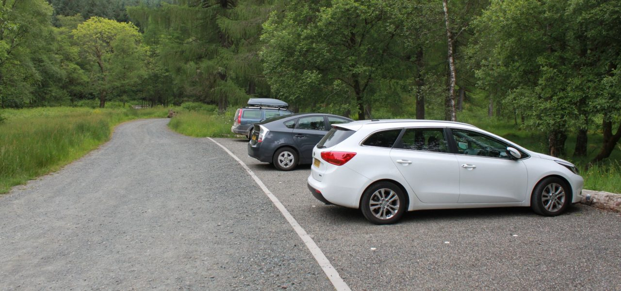 loch-chon-campsite-parking-spaces-next-to-level-track-with-three-cars-parked-on-the-right-of-the-picture-the-area-is-surrounded-by-lush-green-forest