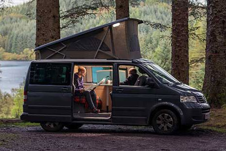 motorhome-parked-at-three-lochs-forest-drive-with-stunning-view-of-loch-and-coniferous-forests-around-the-door-is-open-and-two-men-sit-inside-one-is-reading-a-newspaper