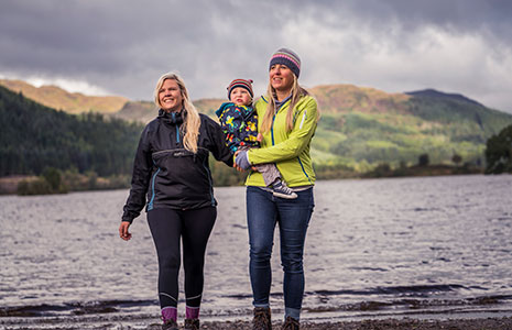 two-women-on-a-loch-shore-holding-small-child-all-smiling
