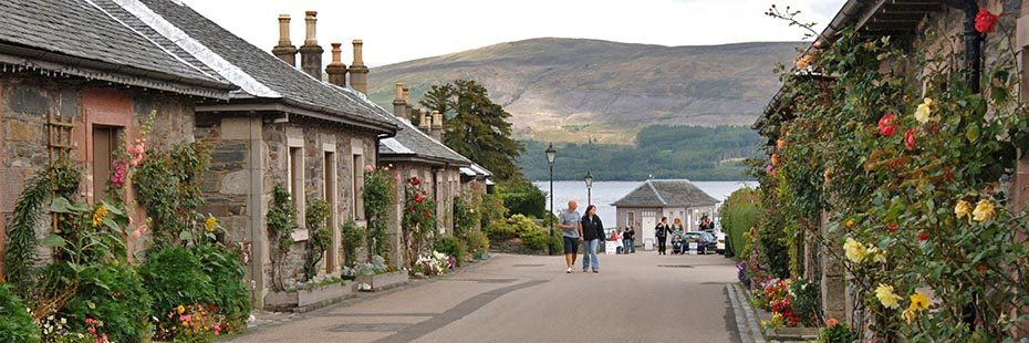 luss-village-pier-road-with-loch-lomond-and-tourists-in-the-distance-and-pretty-stone-houses-with-flowers-outside-on-both-sides