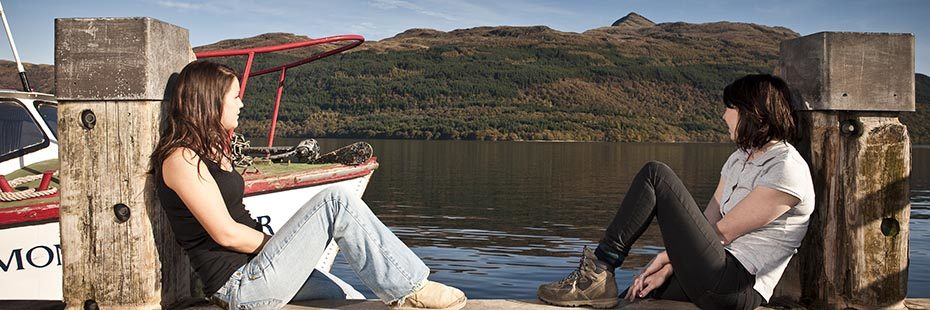 two-young-women-sitting-relaxed-on-edge-of-pier-looking-over-loch-lomond-water-and-ben-lomond-towring-abover-hills-and-forests