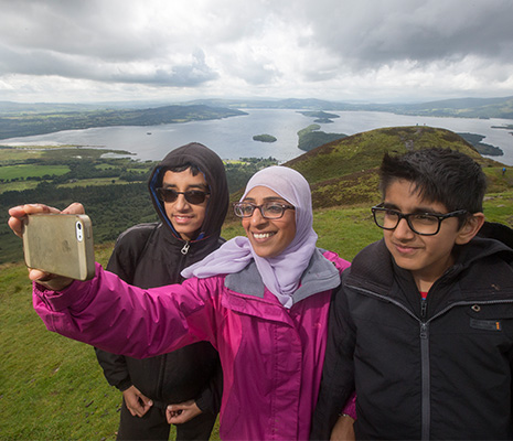 three-young-people-two-boys-and-a-girl-taking-a-selfie-from-the-top-of-conic-hill-overlooking-loch-lomond